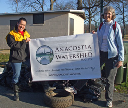 Volunteers Lucrecia and Lisa hold up a banner: Anacostia Watershed Society. clean the water, restore the shores, honor the heritage