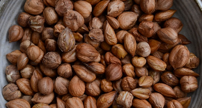 An image filled with several small light brown hazelnuts packed closely together.