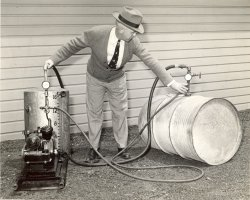 Walkden fumigating: 'H.H. Walden, USDA entomologist, demonstrates the fumigation of stored grain by means of a power compressor. The fumigation tank is filled with the liquid fumigant from a supply drum. May 1942.'