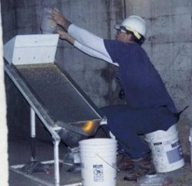 man processing samples on an inclined sieve