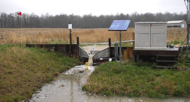 Small field monitoring site in northeast Indiana, with runoff flow through a drop-box weir. Water samples are collected and stored inside the small building.