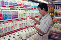 Image of a man browsing in a typical dairy case at a grocery store.