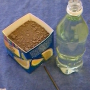 image of soil in a half of a orange juice carton and a soda bottle of water