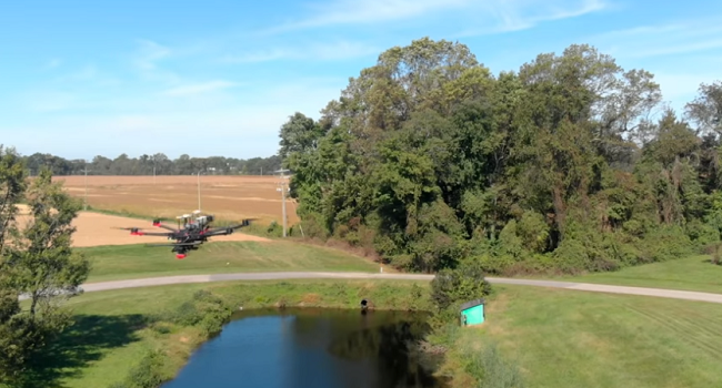 Drone flying over irrigation pond near production fields.