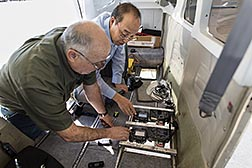 USDA scientists installing digital cameras in a small airplane.