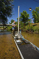 Daniel Wren, standing on the instrument platform that is in a shallow stream, makes adjustments to the platform. Link to photo information