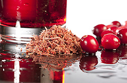 Photo: A glass of cranberry juice, whole cranberries and a pile of cranberry pomace on a table. Link to photo information