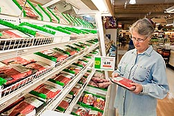 Photo: A woman looking at a package of meat in a grocery store. Link to photo information