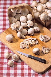 Display of whole and sliced white button mushroooms on a cutting board. Link to photo information