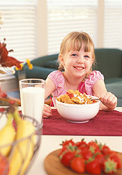 Girl eating breakfast of cereal, milk and fruit. Link to photo information