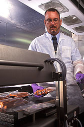 Photo: ARS researcher Christopher Sommers examines packets of hot dogs in a laboratory. Link to photo information
