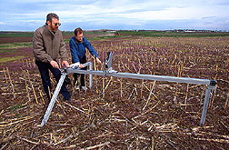 Two researchers use a scanner to measure the amount of corn residue that remained standing after overwintering. Link to photo information