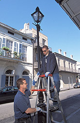 Workers inspect an alate trap on a lamppost in the French Quarter of New Orleans. Link to photo information