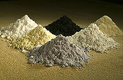 Close-up of six small piles of different rare-earth oxides used as tracers for erosion studies.Photo: Link to photo information