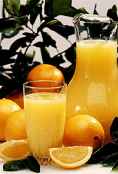 Photo: A pitcher and glass of orange juice is set among fresh oranges. Link to photo information