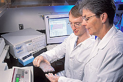 Physiologist Marta Van Loan (right) and chemist Erik Gertz examine a tray of serum samples to be analyzed for markers of bone formation and resorption.