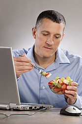 Photo: Man sitting by a laptop computer eating a bowl of fruit. Link to photo information