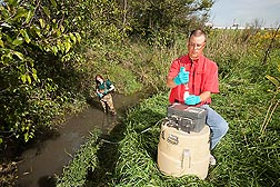 Photo: ARS soil scientist tests stream bed sediments. Link to photo information