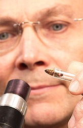 Photo: Entomologist John Harbo prepares a queen bee for artificial insemination. Link to photo information