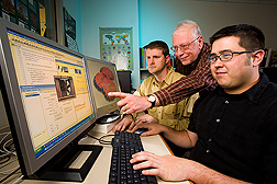 Seated before computer, Jonathan Frantz, James Locke and Byron Hand make modifications to Virtual Grower software program. Link to photo information