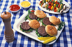 Photo: Four hamburgers on a white plate on a table. Link to photo information