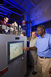 Photo: ARS chemical engineer Akwasi Boateng (right), ARS mechanical engineer Neil Goldberg (center) and ARS chemist Charles Mullen (left) adjust a machine that can make barley leftovers into bio-oil. Link to photo information