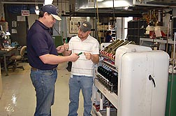 Materials engineer Chris Delhom (left) and technician E.J. Deshotel examine miniature spinning equipment.