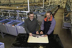 ARS molecular biologist Geoff Waldbieser (left) and geneticist Brian Bosworth inspect a Delta Select channel catfish.  Link to photo information