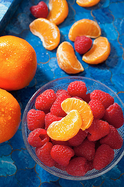Red raspberries and mandarin oranges on a blue tray