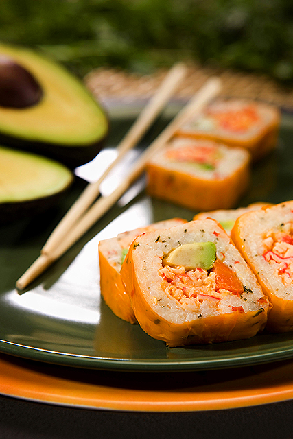 carrot-ginger wrap around a sunny California roll on a plate with chop sticks and an avocado