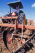 Field technician driving tractor-drawn stalk puller