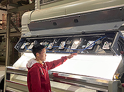 A technician performs system tests on the Visual Inspection Plastic Removal system on a cotton gin