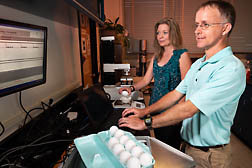 scientists in test kitchen weighing eggs
