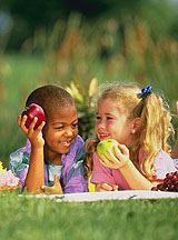 Photo: Little boy and girl eating apples