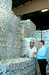 Photo of two men standing in front of stacks of paper for recycling.