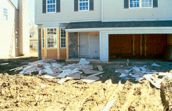 Photo showing wallboard waste in front of a new home that is being built.