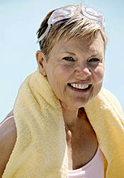 Smiling older woman, towel around neck, who has just finished her swimming workout.