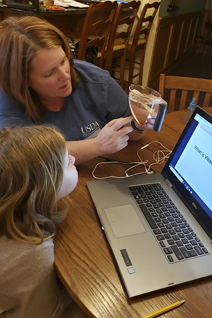 Mother and daughter perform a science activity involving erosion by water