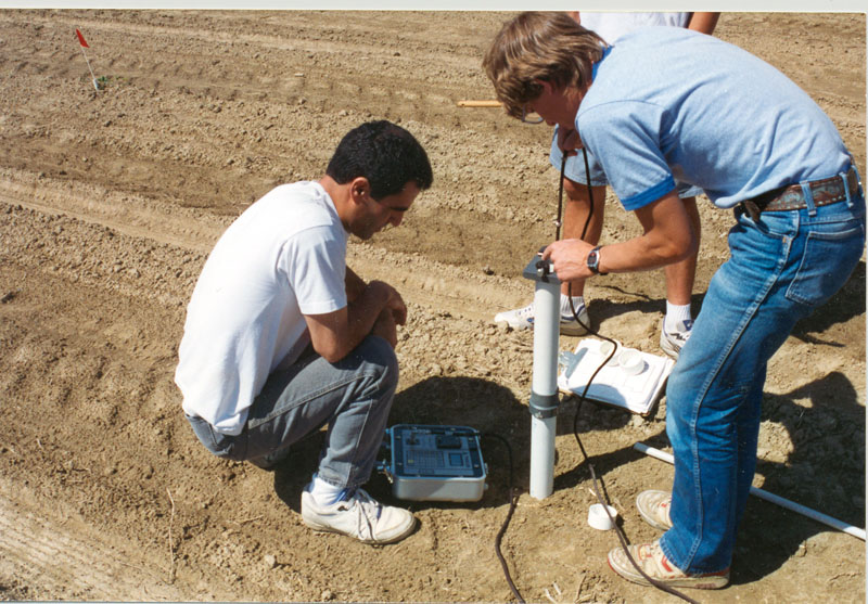 Employees use capacitance probe to test soil water levels