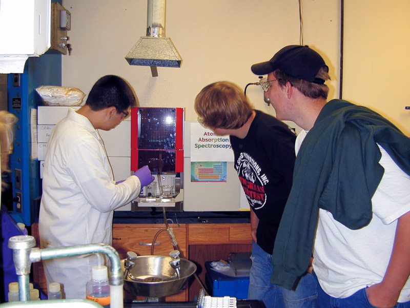 Students operating lab equipment on school tour