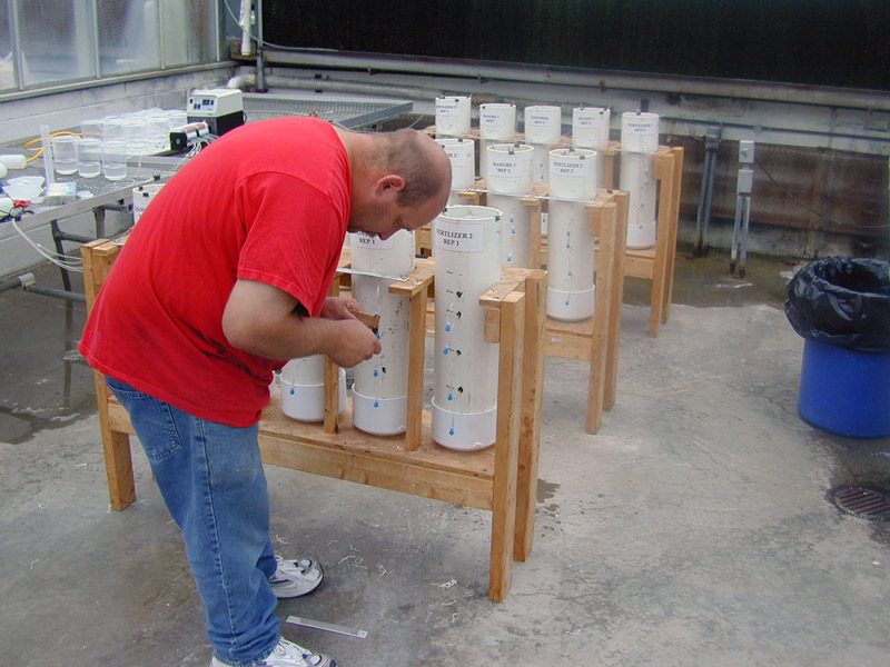 Employee prepares soil columns for research