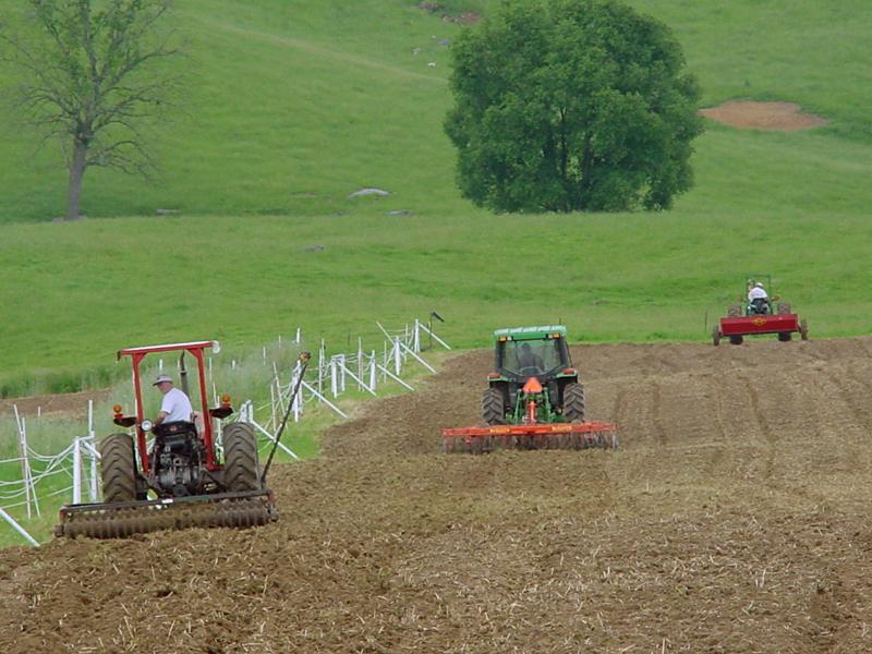Tractors plowing field plot
