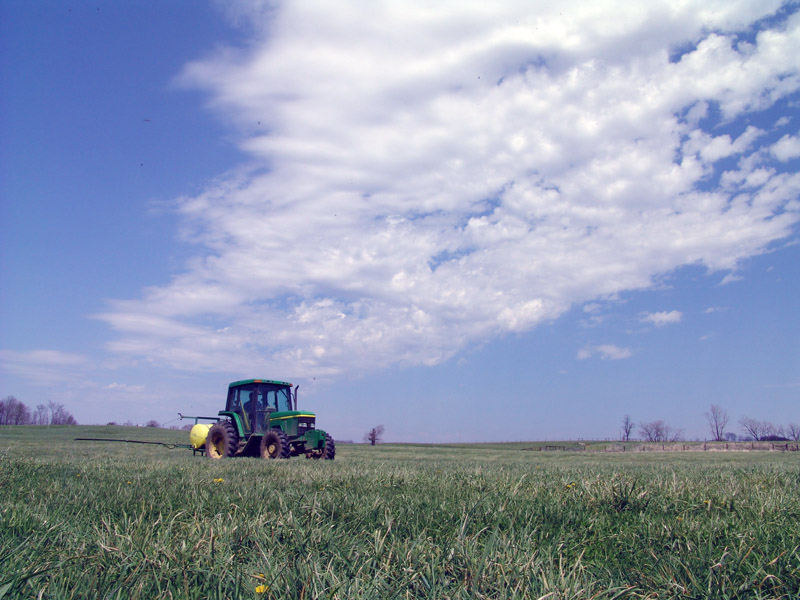 Employee on tractor spraying field