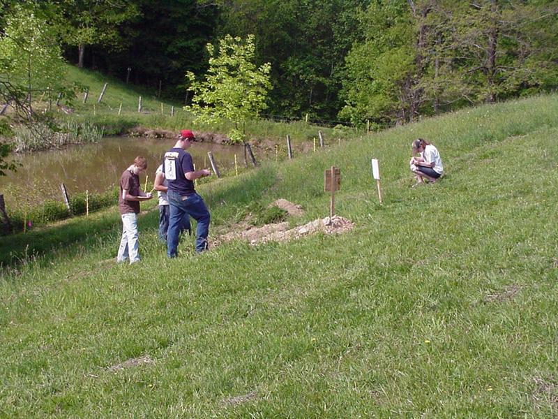 Students judging soil on hillside