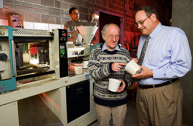 Using an injection molder at the Environmental Management and Byproduct Utilization Laboratory, chemist Walter Schmidt (center) works with colleagues to produce biodegradable flowerpots from chicken feathers. Photo by Stephen Ausmus.