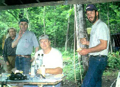 Dr. Victor Kuznetsov (second from left), Dr. Tom Rinderer (middle) and Gary Delatte (right) inspect bees under a microscope for the presence of Varroa.
