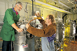 Microbiologist and technician add microorganisms to bioreactors: Click here for full photo caption.