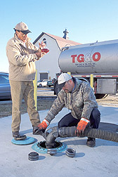 Quality assurance specialist examines a sample of biodiesel while a driver fills a tank: Click here for full photo caption.