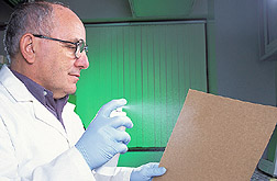 Chemist spraying zein-lipid mixture onto brown kraft paper: Click here for full photo caption.