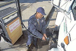 Electrician fills tank of a truck with diesel: Click here for full photo caption.